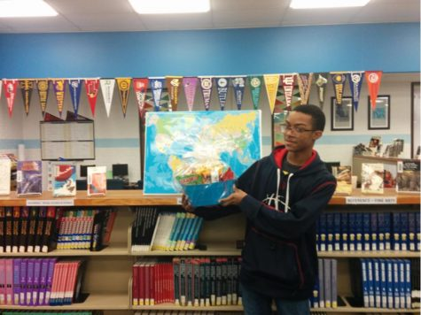 "Pictured with the raffle basket in front of the ""Where in the World"" display is Bryan Ingram, a student in Ms. Erin Johnson's French 1 class."